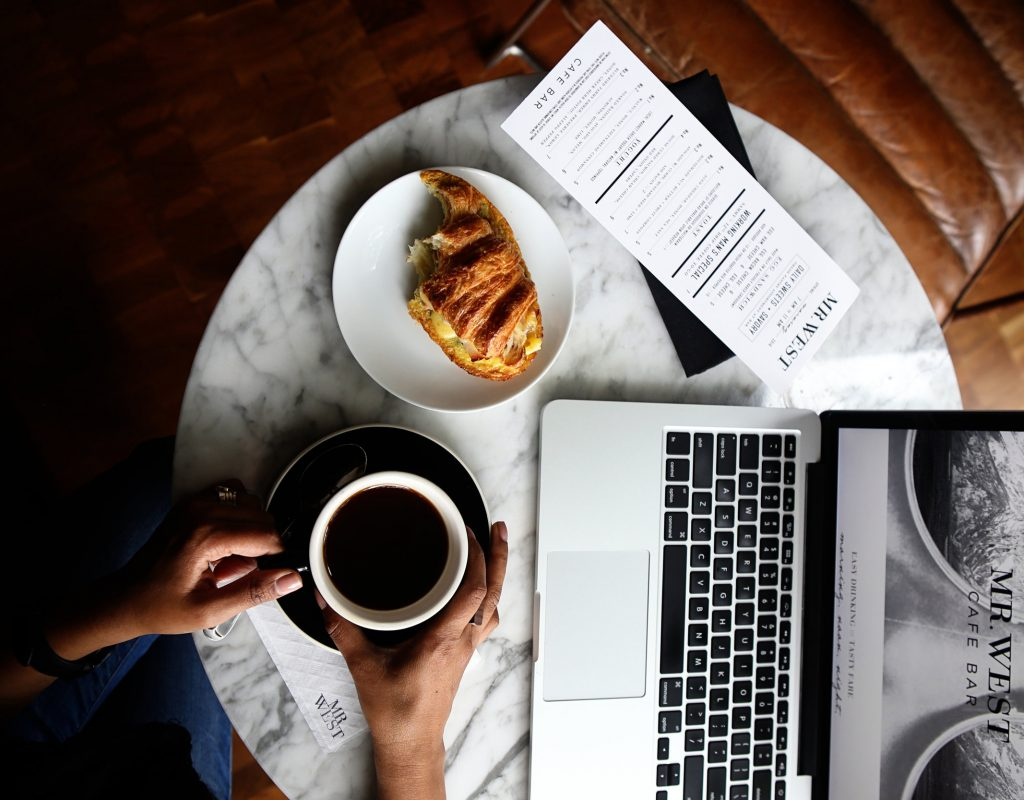 Canva - Macbook Pro and a Cup of Coffee on Table